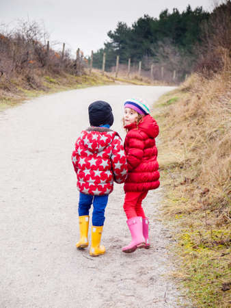 togther: small boy and girl in winter clothing walking hand in hand along a path througha wooded landscape