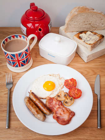 English breakfast opf bacon eggs and sausage on a wooden table with teapot, cup pf tea, butter dish and toast  photo