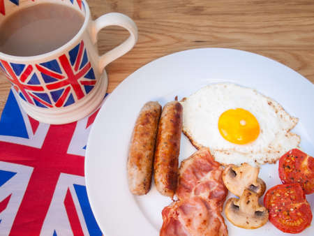 English fried breakfast with cup of english tea in union jack mug and british flag photo