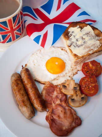 English fried breakfast on a white table top with cup of tea in union jack mug, buttered toast  and british flag behind photo