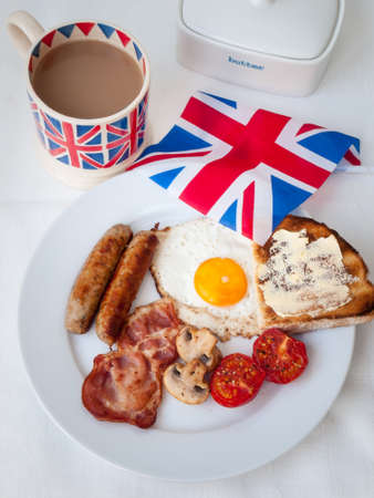 English fried breakfast on a white table top with cup of tea in union jack mug, buttered toast , butter dish and british flag