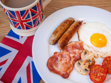 english breakfast: Close-up of cooked English Breakfast on a wooden table with cup of tea  and union jack flag behind Landscape  Stock Photo