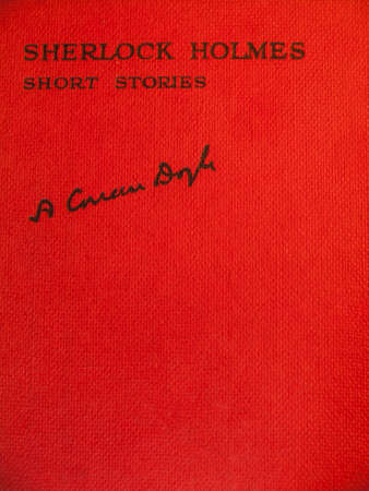 Red front cover of aged  of volume of sherlock holmes  stories carrying the title sherlock holmes short stories and the signature of sir arthur conan doyle