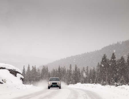 four wheel drive: four wheel drive vehicle driving down a snow covered road during a heavy snow storm in the winter. Stock Photo