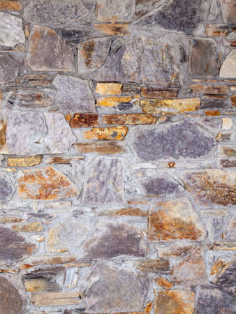 masonary: architechtural detail of grey, yellow and brown stone built wall