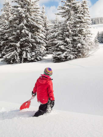 small girl walking in deep snow with sledge in hand and wooded winter  mountain landscape behind photo