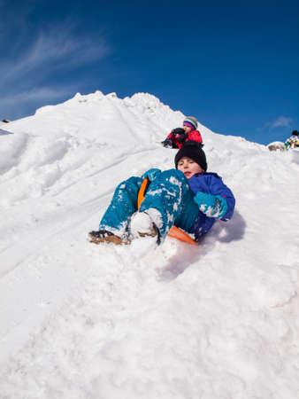 sledging: piccolo ragazzo felice slittino veloce gi� una neve ripida collina ricoperta con la bambina e il cielo blu dietro Archivio Fotografico