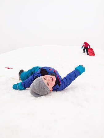 sledging: piccolo ragazzo sorridente sdraiato sulla neve in teh piedi di una collina slittino