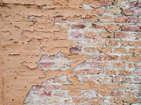 flaking: detail of old brick wall with flaking brown paint