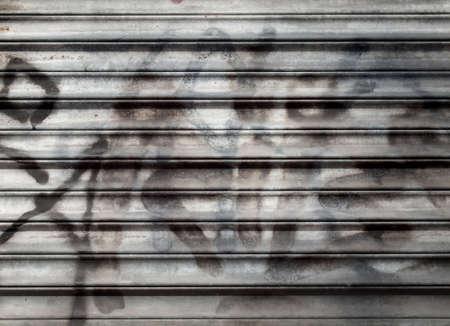 Close-up van grijze metalen rolluik met zwart vervaagde grafiti en diepe schaduwen