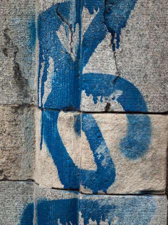 Detail van ruwe geweven grijs metselwerk met blauwe verf grafiti Stockfoto