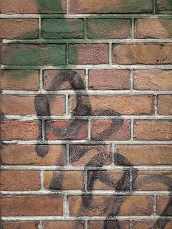 detail van rode bakstenen muur wth grijze mortel en verf grafiti in zwart en groen