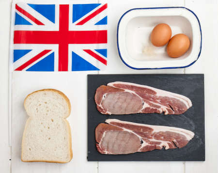 raw thick cut back bacon rashers with eggs and sliced white bread on a rustic white table top with a british flag photo