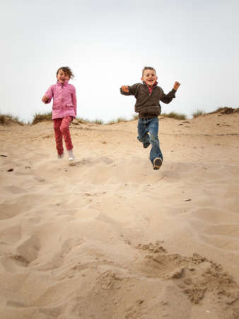 small boy and girl running towards cameradown a sand dune landscape in spring photo