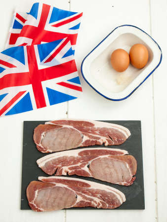 preperation: three raw thick cut back bacon rashers with eggs on a rustic white table top with a british flags Stock Photo