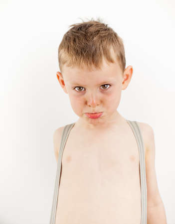 portrait of a small boy looking grumpy wearing braces over a bare chest  photo
