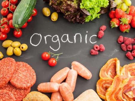 obst und gem�se: rohes Fleisch mit frischem Obst, Gem�se und Brot auf einer Tafel tragen das Wort Bio-