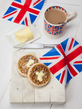 English crumpets with butter on a rustic white table top with a cup of english tea in a union jack mug and british flags photo