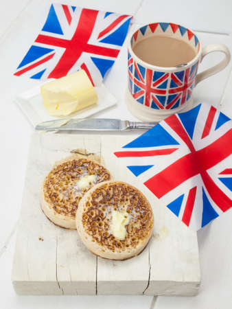 English crumpets with butter on a rustic white table top with a cup of english tea in a union jack mug and union jack flags photo