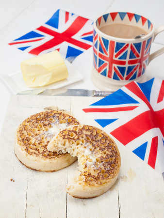 Close up of half eaten English crumpets with butter on a rustic white table top with a cup of english tea in a union jack mug and union jack flags photo