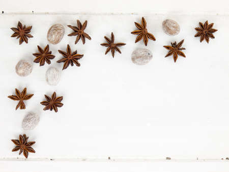 arrangment: an arrangment of star anise and nutmeg on a rustic white table top with copy space Stock Photo