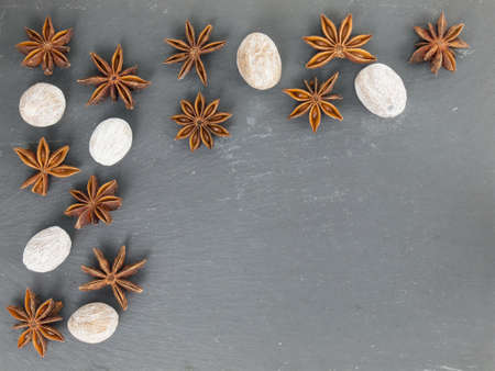 arrangment: an arrangment of star anise and nutmeg on a black slate with copy space