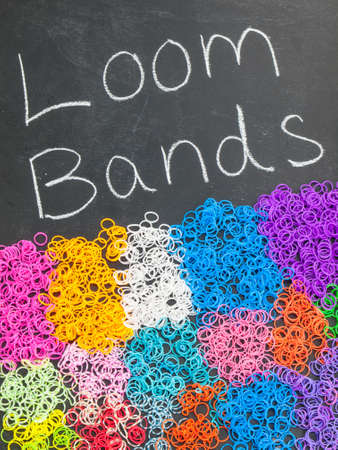 multicolored loom bands on a blackboard with the text loom bands
