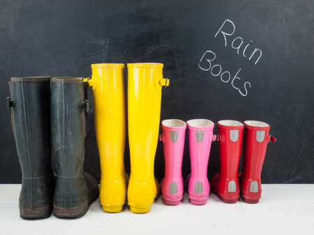 rain boots: four pairs of colourful rubber rain boots  on a white rustic floor infront of a blackboard with the text  rain boots