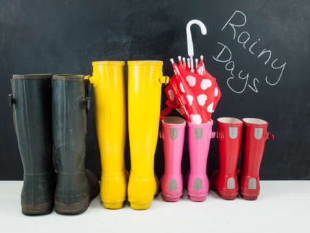 four pairs of colourful rubber rain boots  and a childs umbrella on a white rustic floor infront of a blackboard with the text rainy days photo