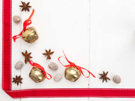 arrangment: arrangment of star anise and nutmeg with sleigh bells and red ribbon on a rustic, aged, white wooden table top Stock Photo