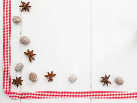 arrangment: arrangment of star anise and nutmeg with checked red ribbon on a rustic, aged, white wooden table top