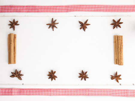 frame of star anise  with cinamon sticks and checked red ribbon on a rustic, aged, white wooden table top photo