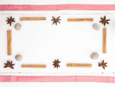 frame of star anise  and nutmeg with cinamon sticks and checked red ribbon on a rustic, aged, white wooden table top photo
