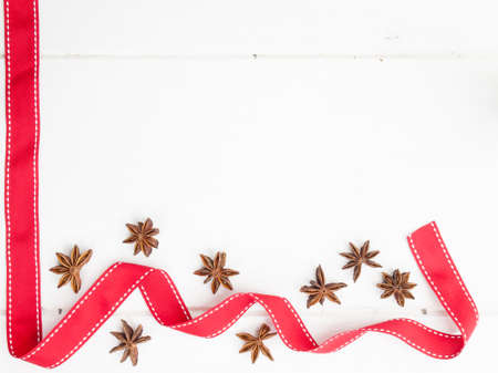 arrangment: arrangment of star anise with red ribbon on a rustic, aged, white wooden table top