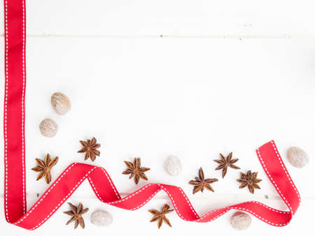 arrangment: arrangment of star anise and nutmeg with red ribbon on a rustic, aged, white wooden table top