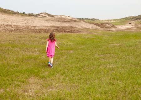 niños caminando: pequeña niña de cabello rizado con un vestido rosa de verano, caminando en una Landcsape duna cubierta de hierba Foto de archivo