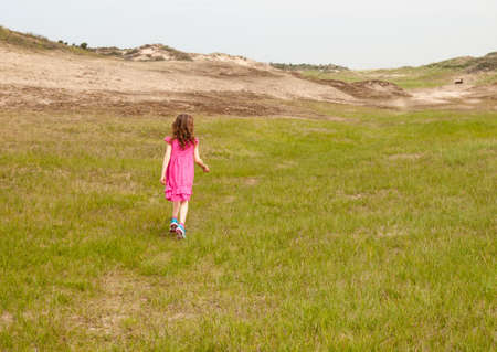small curly haired girl in a pink summer dress, walking into a grassy dune landcsape photo