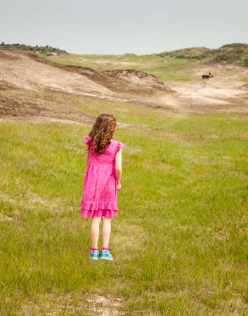small curly haired girl in a pink summer dress, standing in a grassy dune landcsape with deer in the distance photo