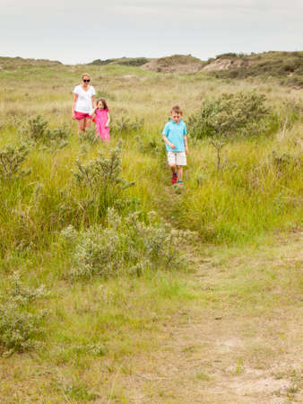 mother and two small children walking through a grassy dune landscape, photo