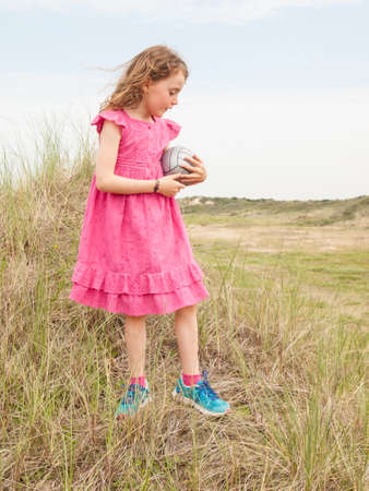 small curly haired girl in a pink summer dress, standing in a grassy dune landcsape holding a ball photo