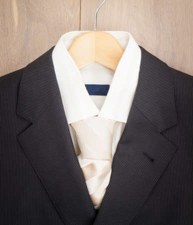 taylor: detail of mens suit jacket  shirt and tie on a hanger agaist wooden wardrobe background