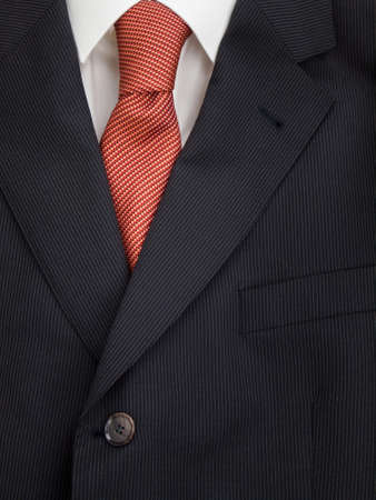 taylor: detail of mens pinstripe suit jacket lapel with  shirt and orange speckled tie Stock Photo