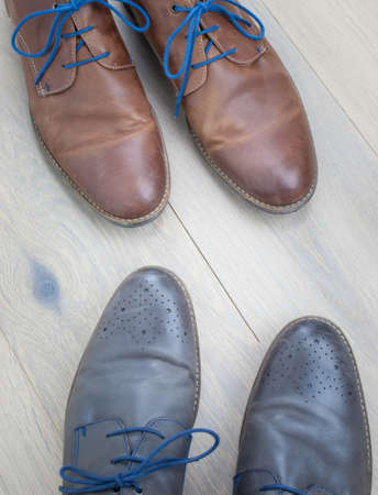 detail of two pairs of grey and brown  leather shoes toe to toe against an aged oak floor photo