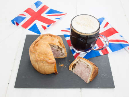 sliced english pork pie and a glass of beer on a black slate with rustic white table top behind and union jack flags photo