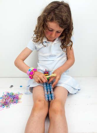 banding: small girl in summer dress wearing  loom band braclets loom banding