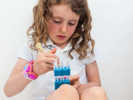 braclets: close up of small girl wearing a loom band braclets concentrating hard while loom banding Stock Photo