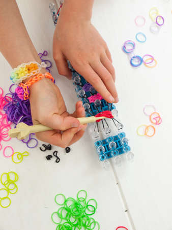hooking: childs hands hooking colourful elastic loom bands with a croche hook on a band loom against a white table top