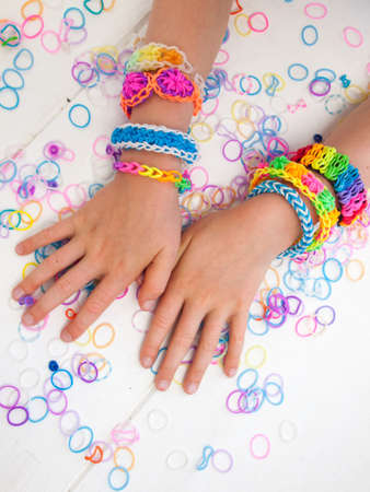 colourful elastic loom band bracelets worn on  a child hands  against a white table top photo