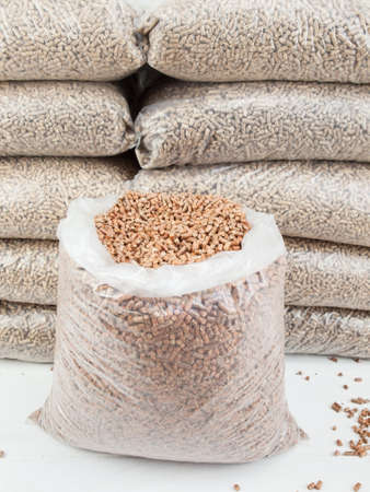 bagged: An open bag of wood pellets with a stack of bagged wood pellets in storage behind