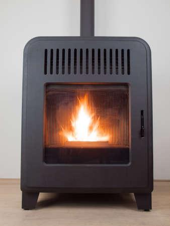 estufa: una estufa de pellet dom�stico moderno con una llama ardiente